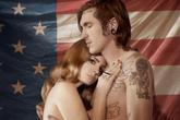 Topless Lana del Rey embraced by a tattooed man in front of the American flag.