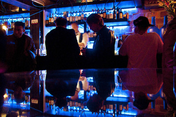 Men drinking at the reflective bar at Slowly in Florence.