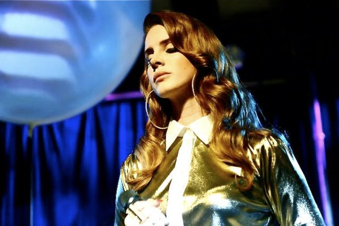 Lana del Rey on stage in a shiny gold top and hoop earrings.